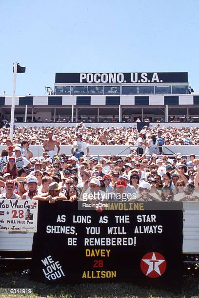 Fans display homemade banners honoring the late Davey Allison during the running of the Miller Genuine Draft 500 NASCAR Cup race at Pocono...