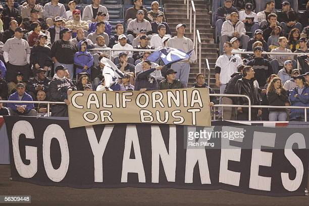 Fans display signs reading California or Bust and Go Yankees during Game Four of the American League Division Series between the Los Angeles Angels...
