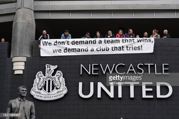 Fans drape a banner over the club sign as Newcastle United play their first game since the club's takeover on October 17, 2021 in Newcastle upon...