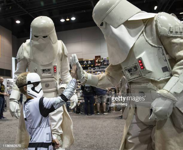 Fans dressed as characters high five during the Star Wars Celebration event at McCormick Place convention center in Chicago Illinois US on Friday...