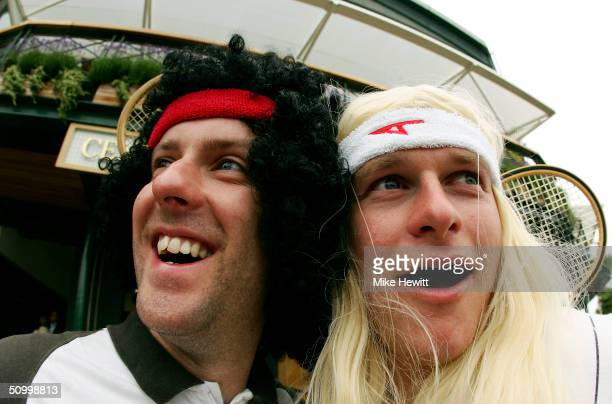 Fans, dressed as former Wimbledon tennis champions John McEnroe and Bjorn Borg, pose for a picture as they wait for play to start during a rain delay...