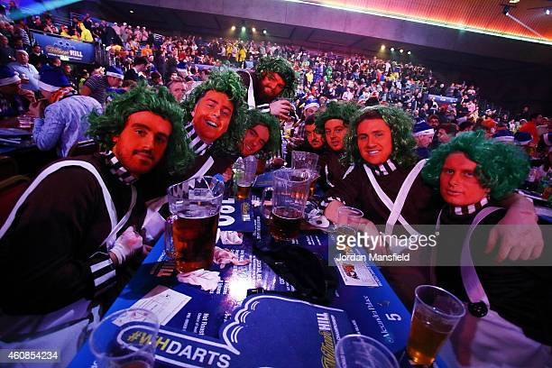 Fans dressed as Oompa Loompa's enjoy the atmosphere during Day Seven of the William Hill PDC World Darts Championships at Alexandra Palace on...