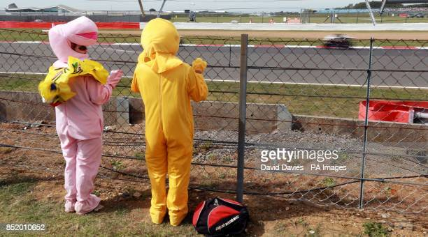 Fans dressed as Zippy and Bungle watch the racing during the Moto GP Hertz British Grand Prix at Silverstone Northamptonshire