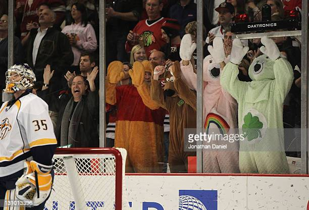 Fans dressed in costumes pound on the glass at Pekka Rinne of of the Nashville Predators after a score by the Chicago Blackhawks at the United Center...