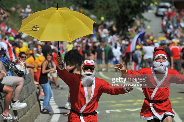 Fans dressed up as Christmas fathers pose with a Tour de France umbrella on July 19 2009 during the 2075 km and fifteenth stage of the 2009 Tour de...