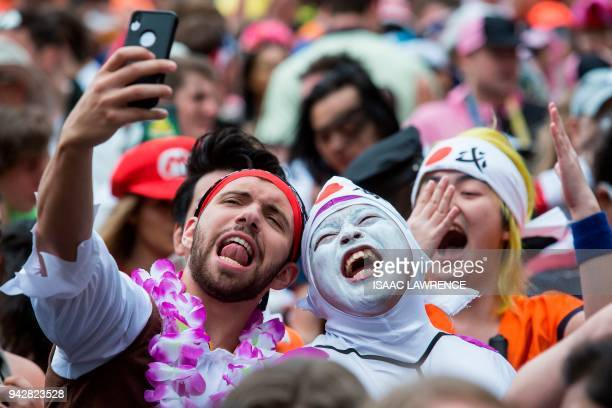 Fans dressed up in costumes pack the South Stand of Hong Kong Stadium early on the second day of the Hong Kong Sevens rugby tournament on April 7...