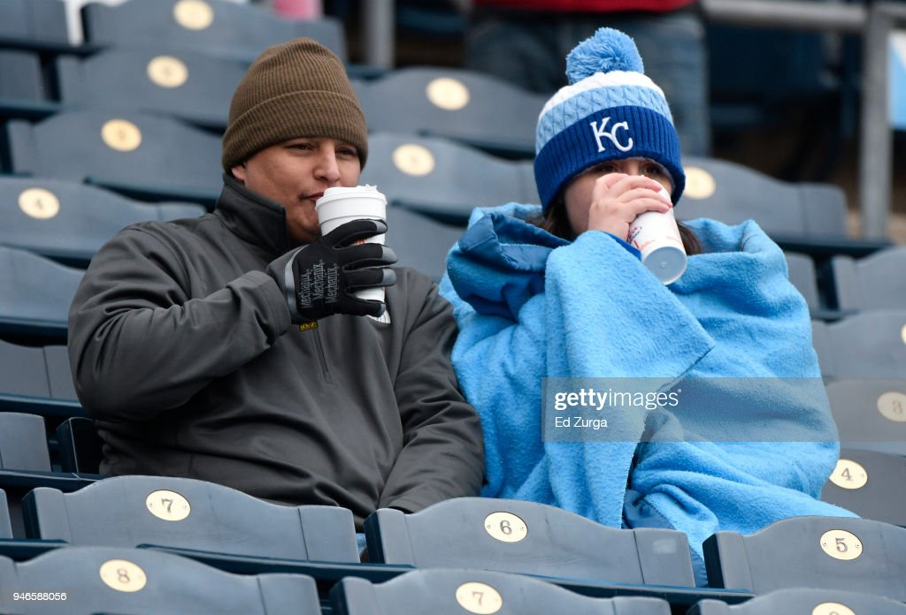Fans drink coffee in an effort to stay warm as they wait for a game between the Los Angeles Angels of Anaheim and Kansas City Royals at Kauffman Stadium on April 15, 2018 in Kansas City, Missouri. The game was postponed due to low temperatures.