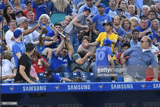Fans duck as a bat flies into the crowd during the regular season MLB game between the Toronto Blue Jays and Tampa Bay Rays on June 13 2017 at Rogers...