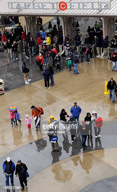 Fans enter Target Field as rain delays the start of the game between the Minnesota Twins and the Kansas City Royals on April 28 2012 in Minneapolis...