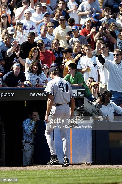 Fans express their opinions as New York Yankees' starter Randy Johnson trudges back to the dugout after being removed from Game 2 of a threegame...