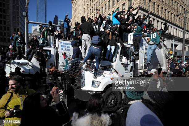 Fans fill the streets as they climb on trash trucks and celebrate with the Philadelphia Eagles during their NFL Super Bowl victory parade on February...