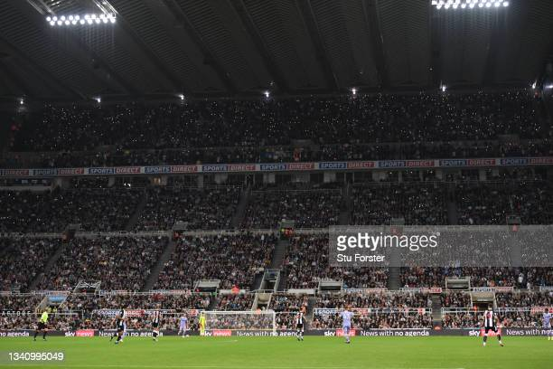 Fans from both teams join to pay homage to Gary Speed by putting their lights on their phones during the Premier League match between Newcastle...
