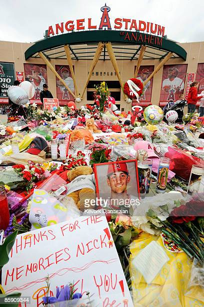 Fans gather around a makeshift memorial to Los Angeles Angels of Anaheim pitcher Nick Adenhart outside Angel Stadium April 10 2009 in Anaheim...