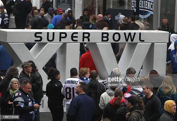 Fans gather around the Roman Numeral Super Bowl number for a photo while visiting the downtown Super Bowl Village