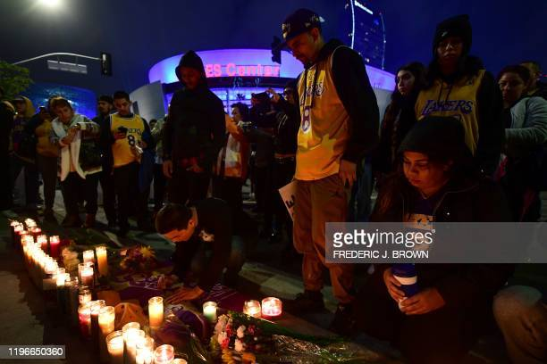 Fans gather at a makeshift candlelight memorial across from Staples center to mourn the death of former Los Angeles Lakers basketball player Kobe...
