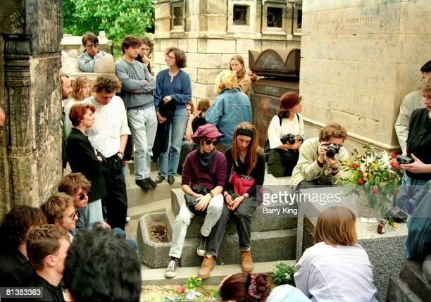Fans gather at Jim Morrison's grave at PereLachaise cemetery in Paris France