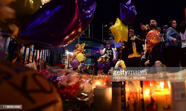 Fans gather in front of a makeshift memorial as they mourn the death of NBA legend Kobe Bryant who was killed along with his daughter and seven...