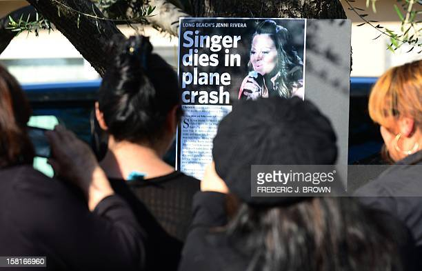 Fans gather in front of a makeshift shrine mourning the death of MexicanAmerican diva Jenni Rivera in front of her home in Lakewood California on...