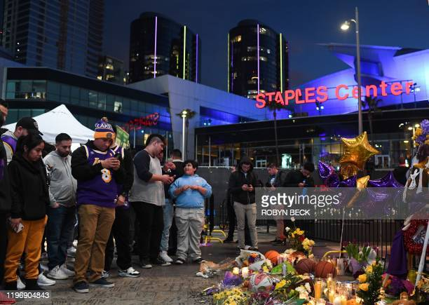 Fans gather near a makeshift memorial as they mourn the death of NBA legend Kobe Bryant who was killed along with his daughter and seven others in a...