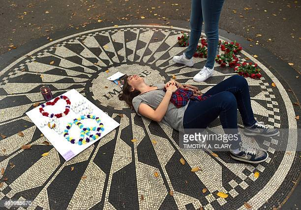 Fans gather on the Imagine mosaic plaque in the Strawberry Fields section of Central Park in New York an area dedicated to the memory of John Lennon...