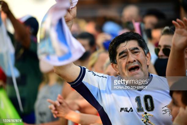 """Fans gather outside the morgue where the late Argentine football star Diego Maradona's body will undergo an autopsy """"to establish the cause of death""""..."""