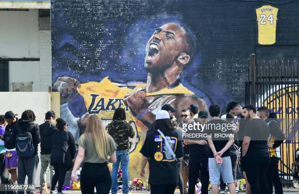 TOPSHOT Fans gather to mourn the death of NBA legend Kobe Bryant at a mural near Staples Center in Los Angeles California on January 27 a day after...