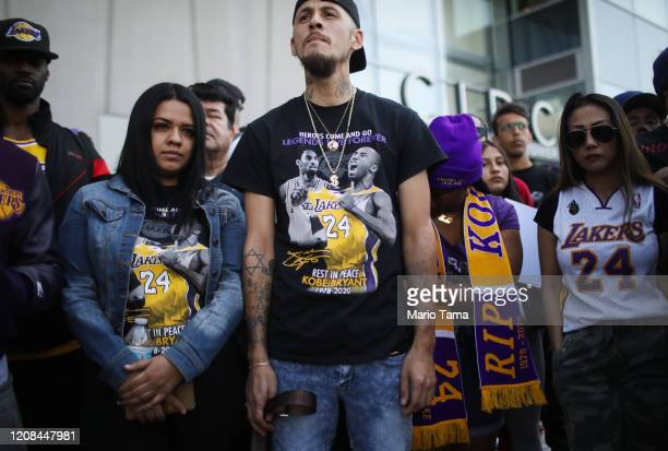Fans gather while watching a live broadcast of the 'Celebration of Life for Kobe and Gianna Bryant' memorial service on a fan's iPad outside the...