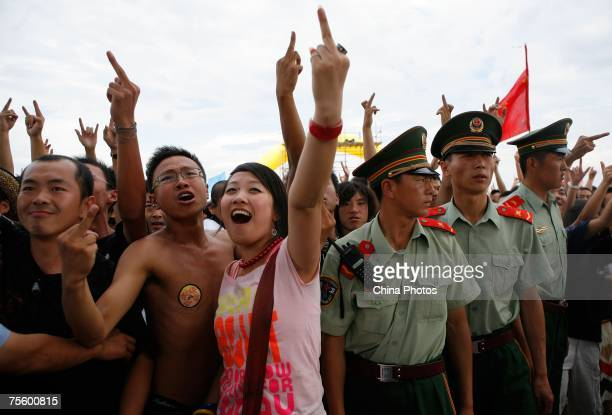 Fans gesture during a performance at the first 'Green Flag Erdos Grassland Rock Music Festival' near the Mausoleum of Genghis Khan on July 21 2007 in...
