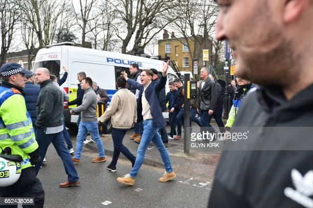 Fans gestures as they arrive at the stadium ahead of the English FA Cup quarterfinal football match between Tottenham Hotspur and Millwall at White...