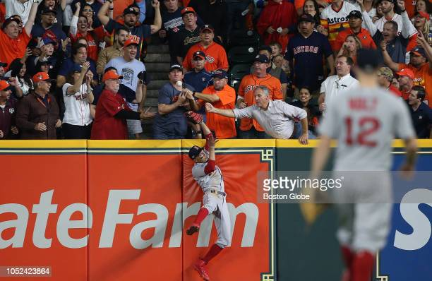 Fans get in the way as Boston Red Sox player Mookie Betts tries to catch a fly ball by the Astros' Jose Altuve in the first inning The Houston Astros...
