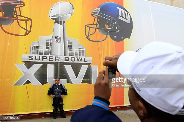 Fans get their photographs made in front of a Super Bowl XLVI logo near Lucas Oil Stadium prior to the game being played between the New York Giants...