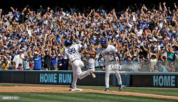 Fans go wild as Manny Ramirez rounds frist base after hitting a 3–run homerun against the Arizona Diamondbacks in the 5th inning at Dodger Stadium in...