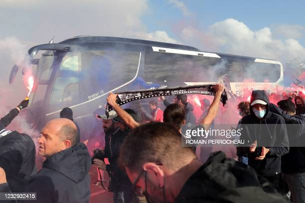 Fans greet the coach carrying the FC Girondins de Bordeaux football players to the stadium before the French L1 football match between FC Girondins...
