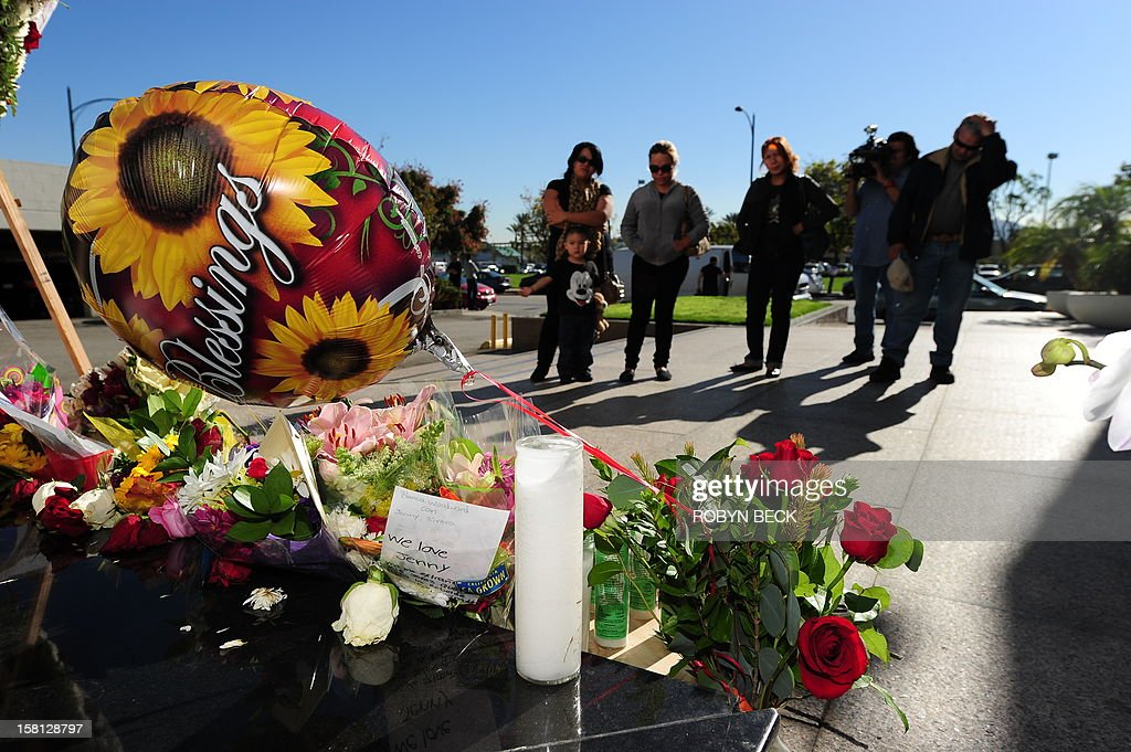 Fans grieve at a memorial of flowers, candles, ballons and notes to the late Mexican-American singing superstar Jenni Rivera, December 10, 2012 in Burbank, California