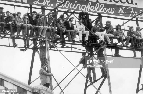 Fans hang sit and stand on a billboard in order to watch Game 1 of the World Series between the Boston Red Sox and Cincinnati Reds at Fenway Park in...