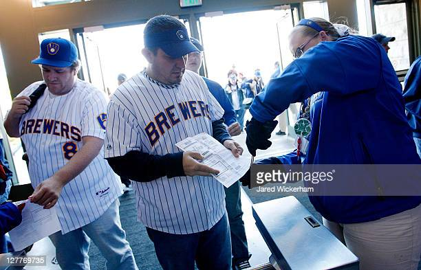 Fans have their tickets scanned as they enter Miller Park prior to Game One of the National League Division Series between the Milwaukee Brewers and...