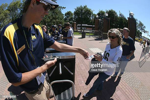 Fans have their tickets scanned as they enter the stadium before the Big Ten college game between the University of Michigan Wolverines and the...