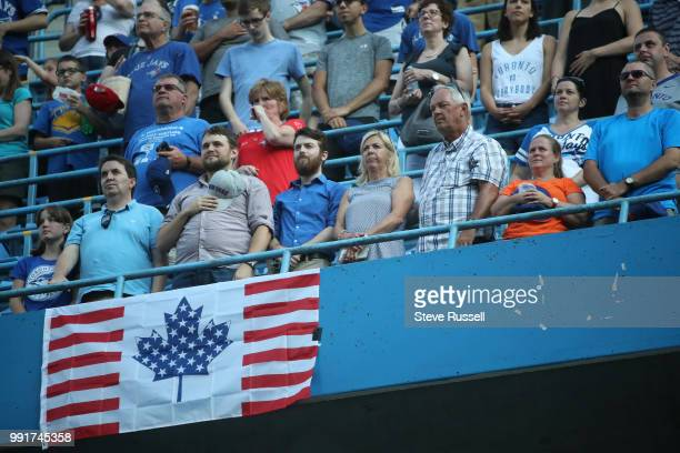 TORONTO ON JULY 4 Fans help celebrate Fourth of July with a hybrid Canadian flag as the Toronto Blue Jays play the New York Mets at the Rogers Centre...
