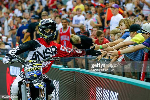Fans 'high 5' the Freestyle Moto X riders during the Big Bash League match between the Melbourne Renegades and the Perth Scorchers at Etihad Stadium...