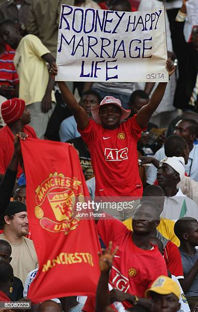 Fans hold a banner wishing Wayne Rooney a happy marriage during the pre-season friendly match between Manchester United and Portsmouth during their...