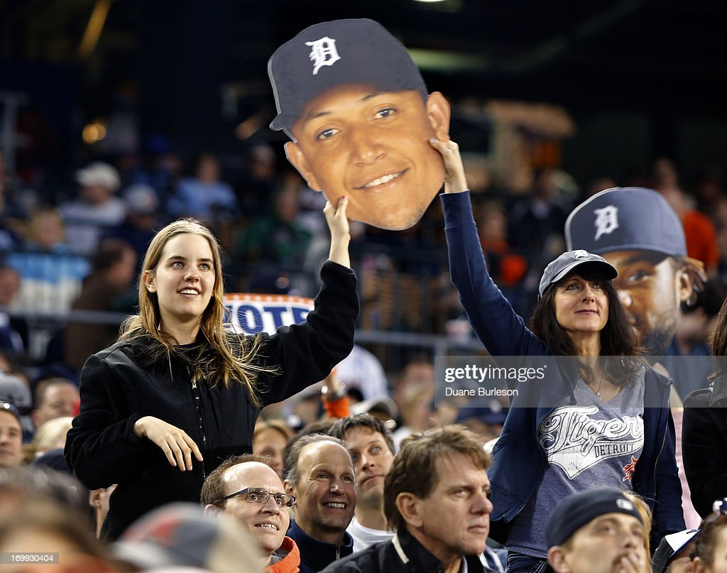 Fans hold a cardboard face of Miguel Cabrera of the Detroit Tigers that were handed out at Comerica Park as part of an All-Star voting campaign on June 4, 2013 in Detroit, Michigan.