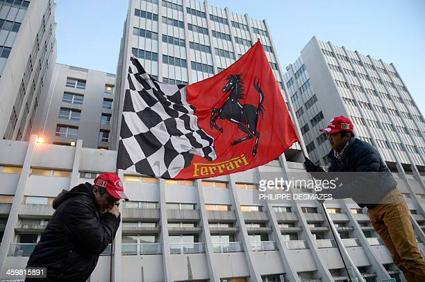 Fans hold a Ferrari flag on December 31 2013 in front of the Grenoble University Hospital Centre in the French Alps where retired seventime German...