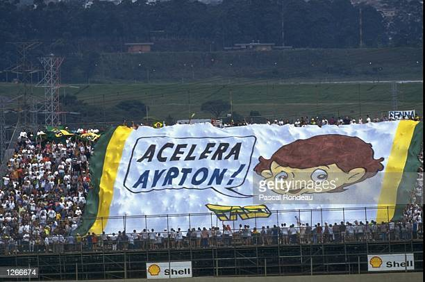 Fans hold a huge flag in support of Williams Renault driver Ayrton Senna of Brazil during the Brazilian Grand Prix at the Interlagos circuit in...