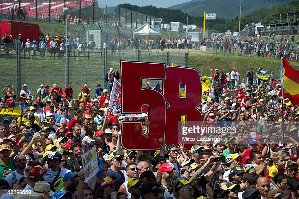 Fans hold aloft the number '58' in memory of former rider Marco Simoncelli as they walk on the track under the podium at the end of the MotoGP race...