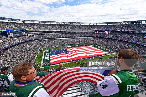 Fans hold an American flag during the National Anthem prior to the game between the New York Jets and the Cincinnati Bengals at MetLife Stadium on...