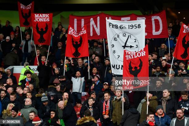 Fans hold banners comemmorating the 1958 Munich Air Disaster in the 60th anniversary year of the crash that killed 23 showing the face of former...