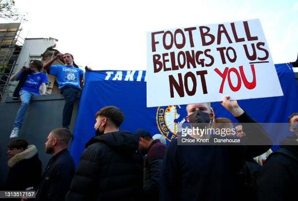 Fans hold banners opposing Chelsea signing up for the newly proposed European Super League ahead of the Premier League match between Chelsea and...
