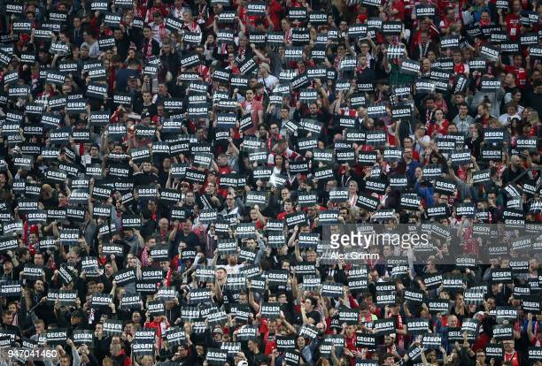 Fans hold cards to protest against monday evening games prior to the Bundesliga match between 1 FSV Mainz 05 and SportClub Freiburg at Opel Arena on...