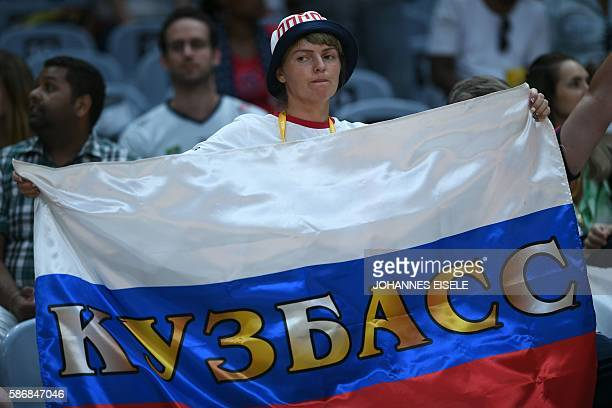 Fans hold flags as they wait for the start of the women's qualifying volleyball match between Russia and Argentina at the Maracanazinho stadium in...