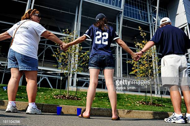 Fans hold hands at the former site of the Joe Paterno statue prior to the Penn State playing the Ohio Bobcats at Beaver Stadium on September 1, 2012...